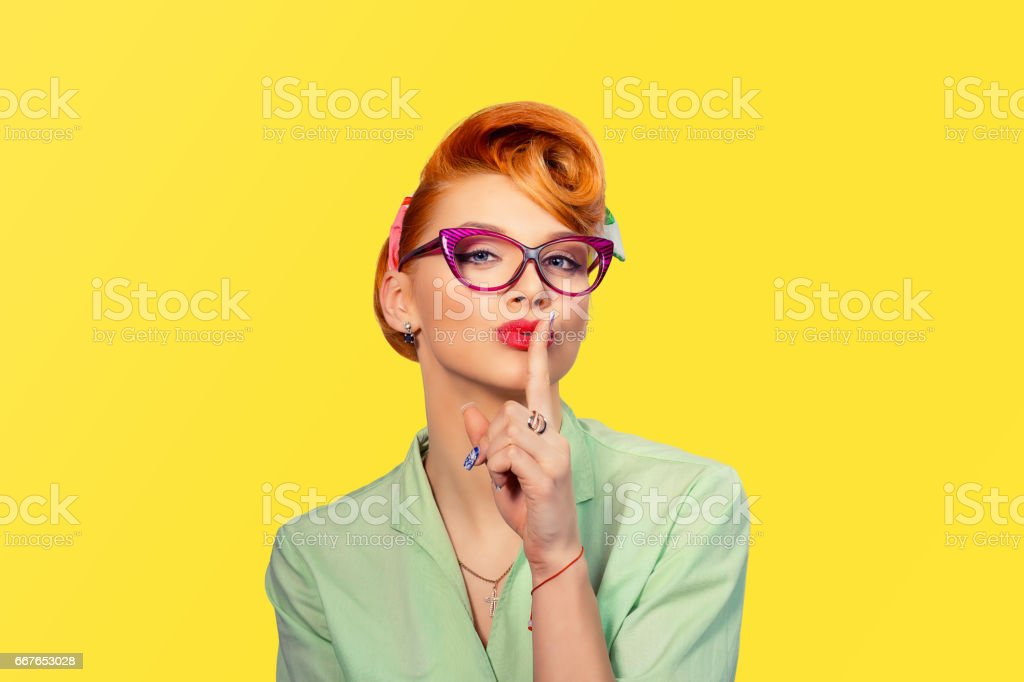 Silence. Woman  asking for silence or secrecy with finger on lips hush hand gesture yellow background wall. Pretty girl placing fingers on lips, shhh sign symbol. Negative emotion facial expression stock photo