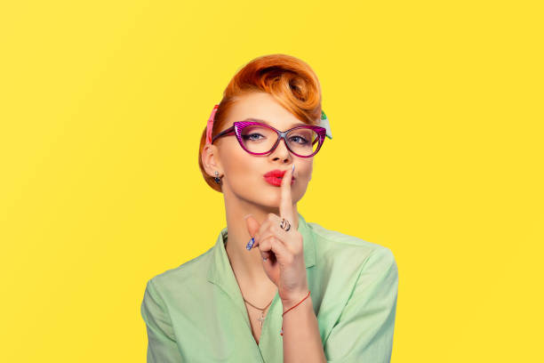 Silence. Woman  asking for silence or secrecy with finger on lips hush hand gesture yellow background wall. Pretty girl placing fingers on lips, shhh sign symbol. Negative emotion facial expression - Photo