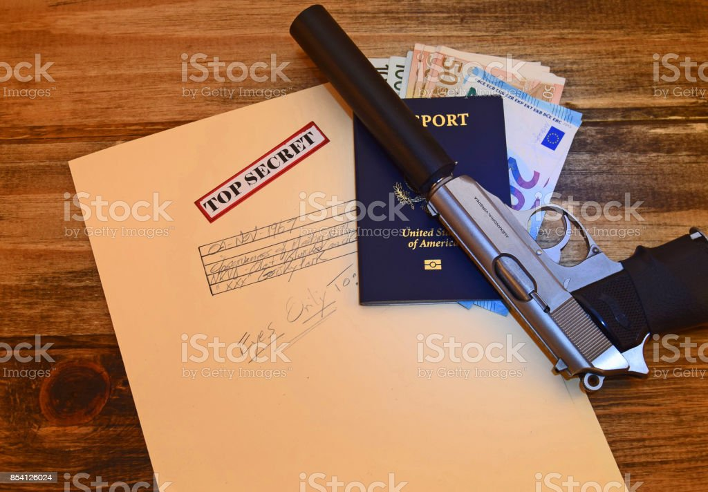 Silenced pistol with passport stock photo