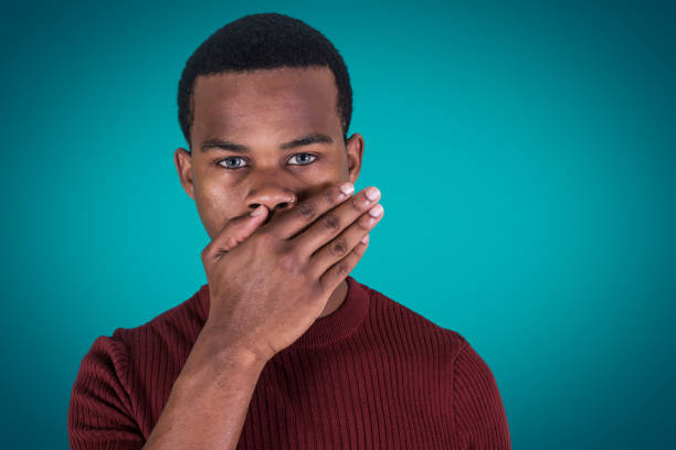 Silent black guy covering mouth Handsome African American guy looking at camera and covering mouth with hand as representation of silence against blue background avoidance stock pictures, royalty-free photos & images