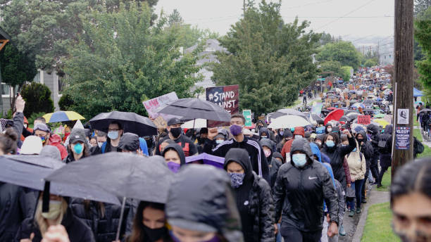 Silent protesters march in the rain through neighborhoods in Seattle calling attention to the Black Lives Matter Movement and Police Brutality stock photo