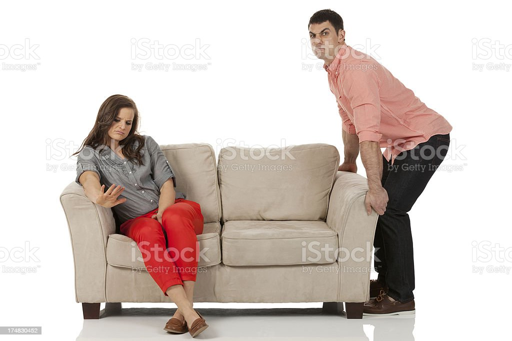 Silent Treatment! Woman sitting on couch ignoring her boyfriend royalty-free stock photo