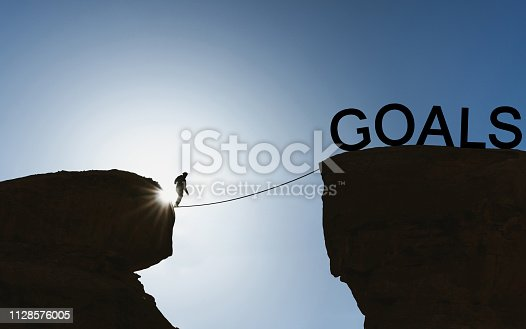 Silhouette a man balancing walking on rope to goals. Life goal, achieve goal concept