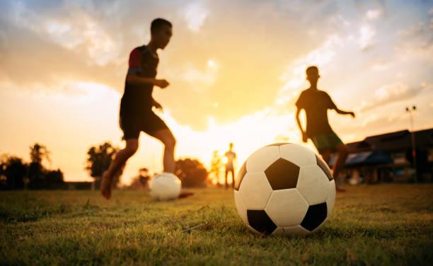 silhouette action sport im freien einer gruppe von kindern, die spaß beim fußballspielen für bewegung in der gemeinde ländlichen bereich unter dem dämmerung sonnenuntergang himmel. - sport stock-fotos und bilder