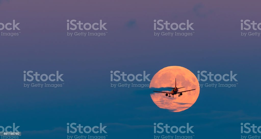 Silhouette airplane at disk of super moon stock photo