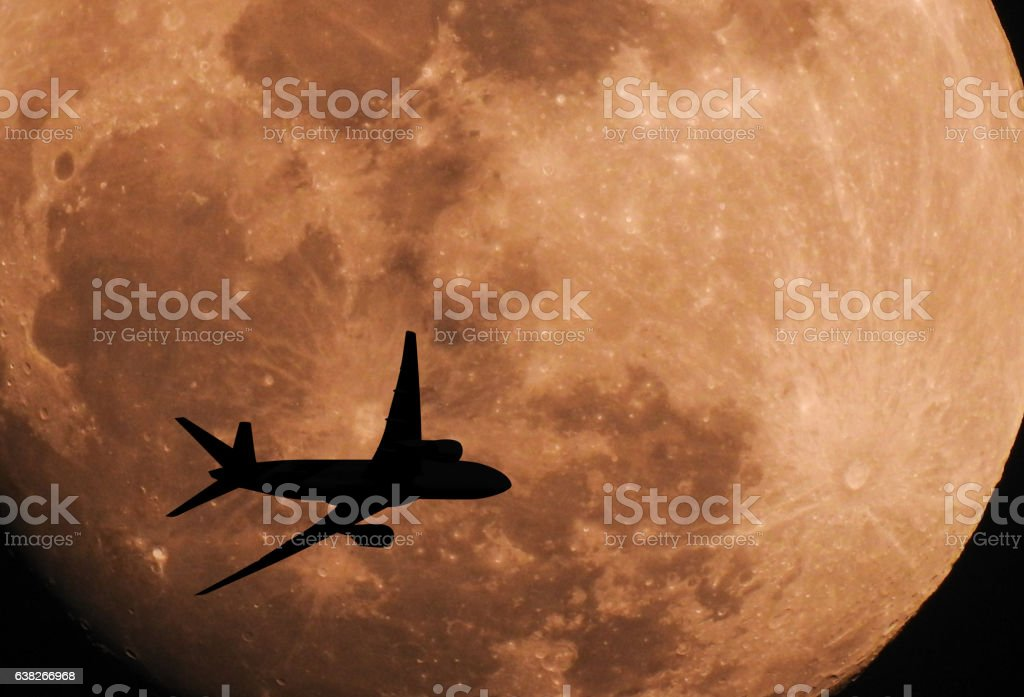Silhouette airplane flying across the moon stock photo