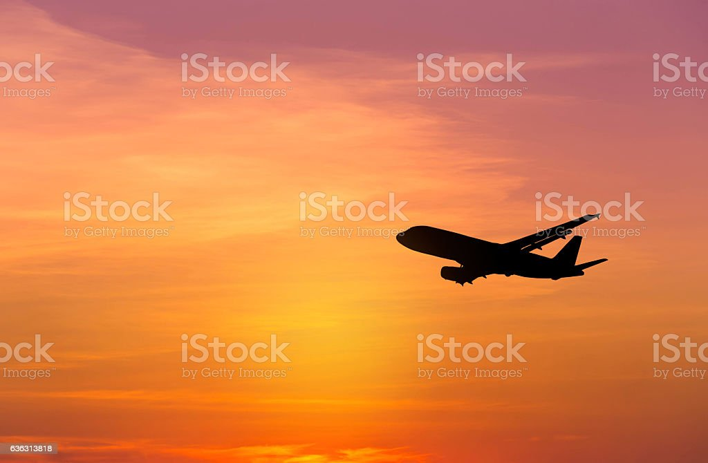 Silhouette airplane flying on sunset stock photo