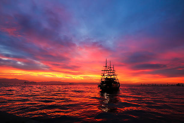 Silhouette an antique ship at a beautiful sunset.