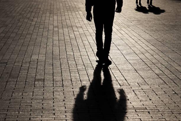 silhouet en schaduw van een eenzame mens die naar een paar op een straat loopt - moordenaar stockfoto's en -beelden