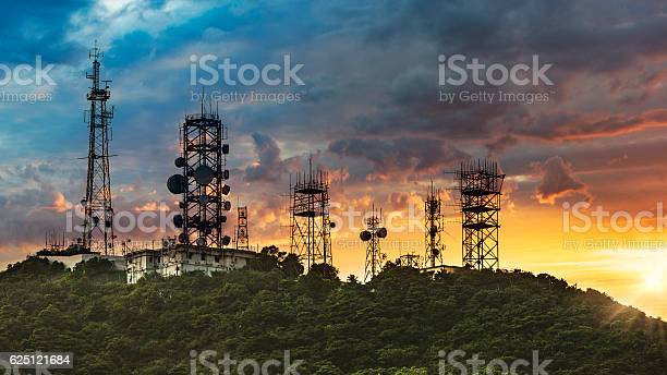 Silhouette Antenna tower and repeater of Communication and telecommunication with the mountain on the background of sunset.Hong Kong China.