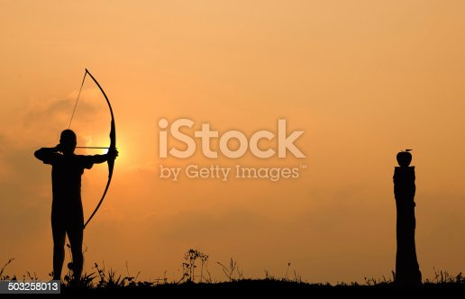 istock Silhouette archery shoots a bow at an apple on timber 503258013