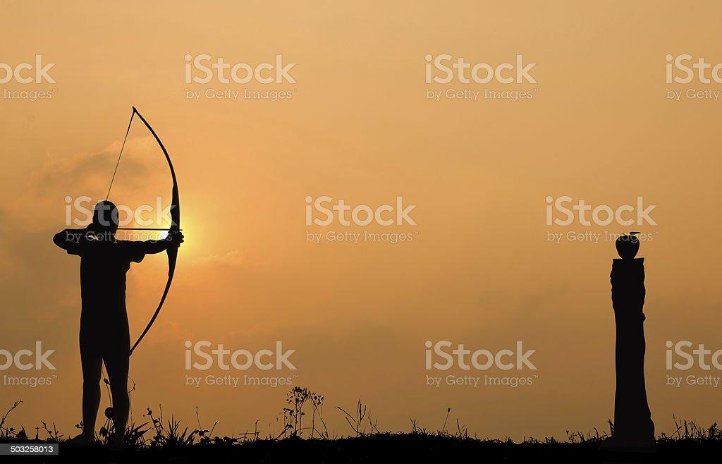 Silhouette Bogenschießen schießt eine Schleife an einem apple auf Holz – Foto