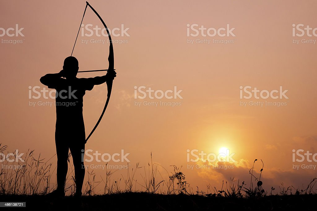 Silhouette archery shoots a bow stock photo
