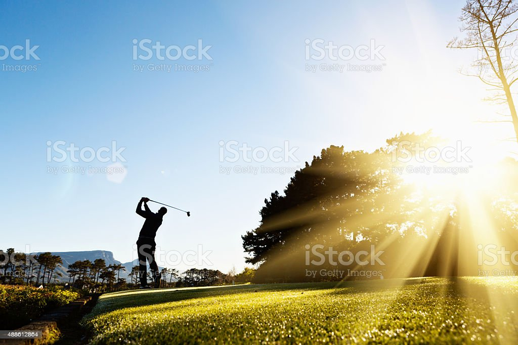 Silhouette as young golfer swings on beautiful, sunlit course stock photo