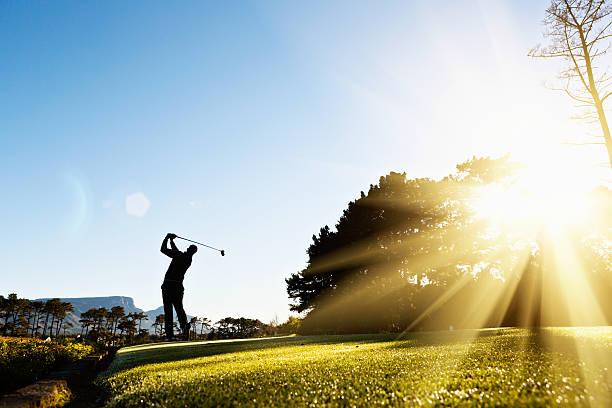 若いゴルファーに揺れ動くシルエットが美しい、自然光が降り注ぐコース - ゴルフ ストックフォトと画像