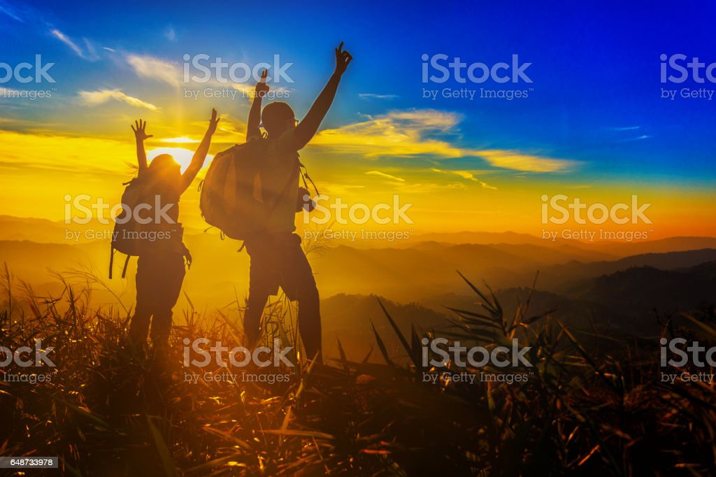 silhouette asian couple backpacker hiking trekking hand up with sunset stock photo