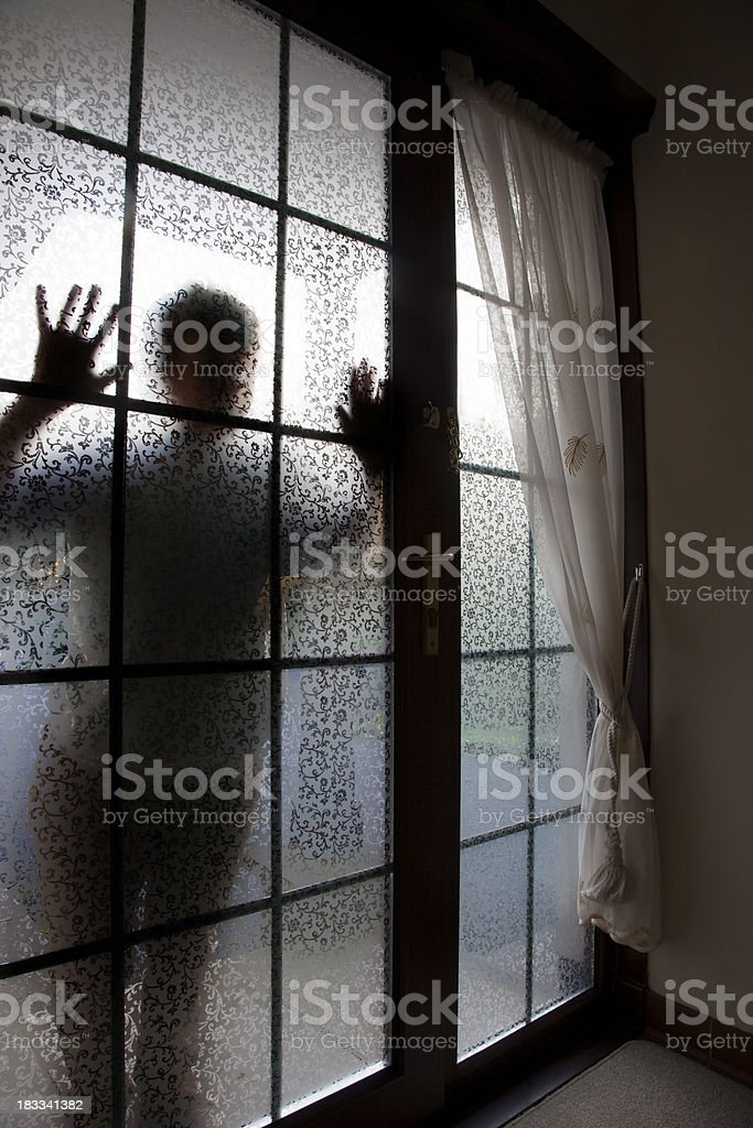 silhouette at frosted glass door stock photo