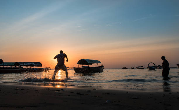 Silhouette at sunset in Zanzibar with boats on Indian Ocean stock photo