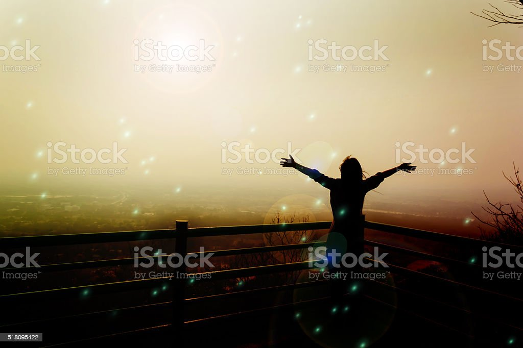 Silhouette back of women raising two arm embracing to sunlight stock photo