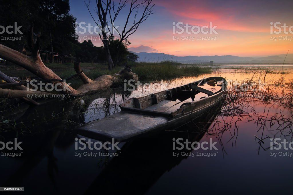 Silhouette de beaux paysages de la nature et les épaves des bateaux de pêche amarré échouée sur la plage pendant la durée de l'aube et le ciel coloré au réservoir de Pra Bang, province de Chonburi en Thaïlande - Photo