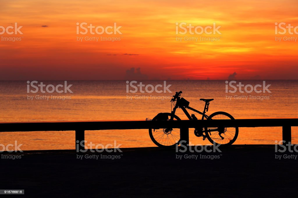 Silhouette bicycle outdoors against sunrise. stock photo