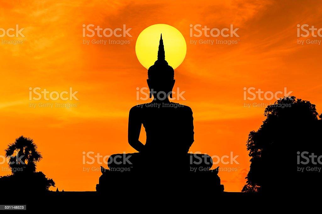 silhouette big buddha statue sitting on sunset stock photo