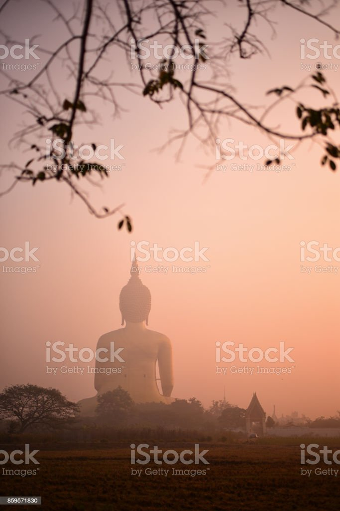 Silueta de big Buddha con el cielo de oro de la puesta del sol y la silueta del hombre manejando una motocicleta con palo de bambú afterwork. - foto de stock
