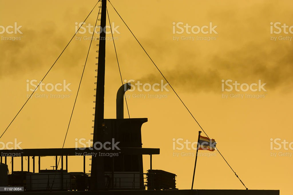 silhouette boat-flue and smoke out to the air stock photo