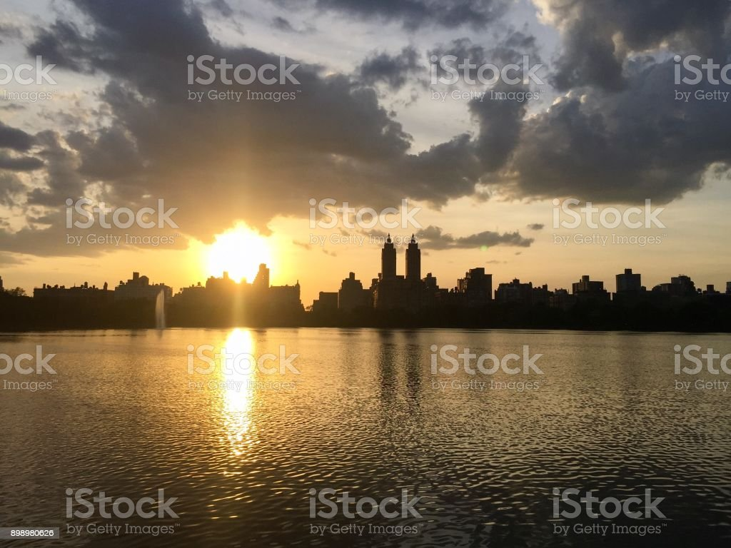 Silhouette Buildings in Manhattan and cloudy sunset sky over lake at Jacqueline Kennedy Onassis Reservoir stock photo