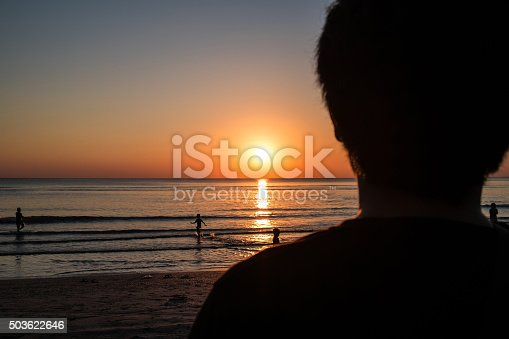 istock Silhouette, close-up rear view of a man standing viewing sunset 503622646