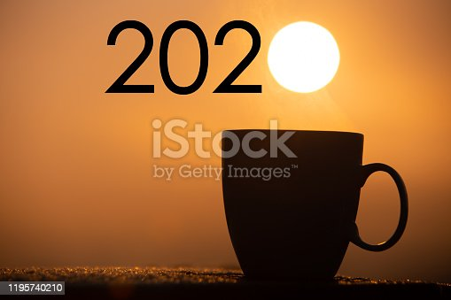 istock Silhouette coffee cup with new year 2020 text on a sunrise background 1195740210