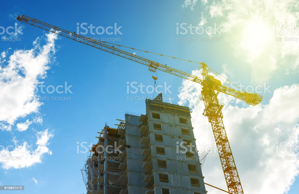 Silhouette construction crane equipment,Industrial construction crane and building over amazing sunset sky abstract background,dramatic clouds behind crane in the evening. stock photo