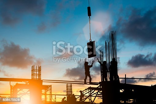 istock Silhouette construction industry team safely to work load concrete building according to set goal over blurred background sunset pastel for industry background. 838475528