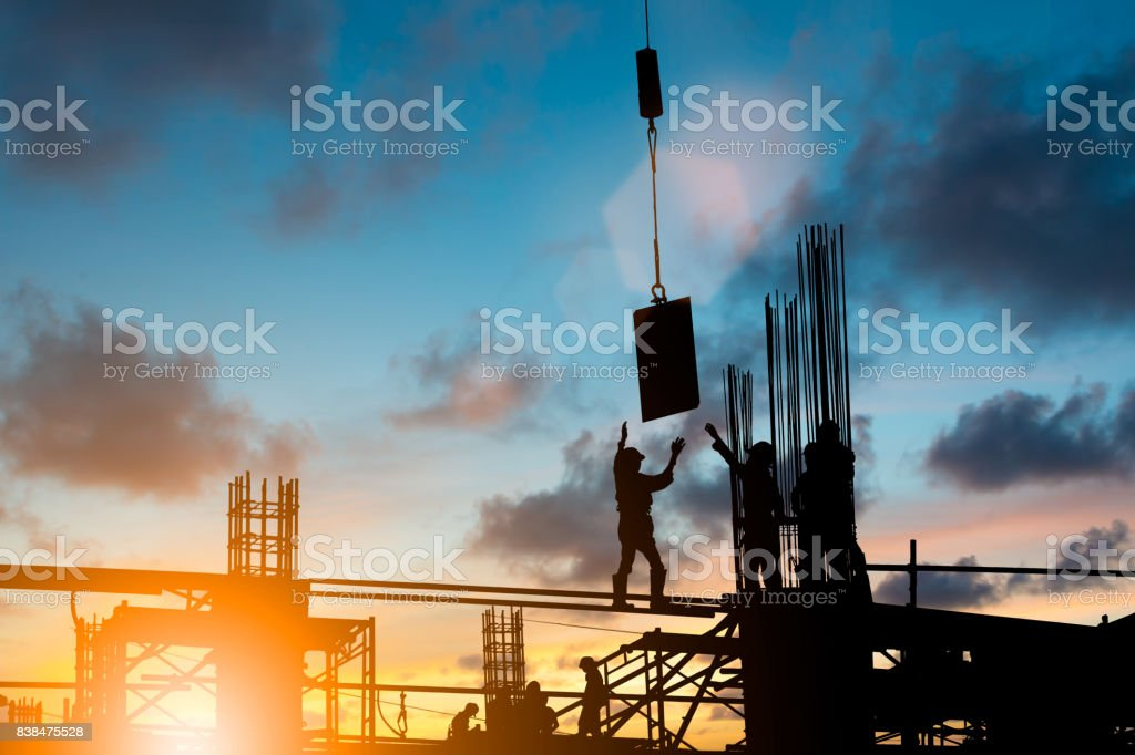 Silhouette construction industry team safely to work load concrete building according to set goal over blurred background sunset pastel for industry background. stock photo