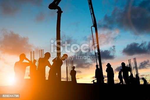 istock Silhouette construction industry team safely to work load concrete building according to set goal over blurred background sunset pastel for industry background. 839044796