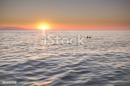 Silhouette couple in love on the sea with a beautiful sunset background.