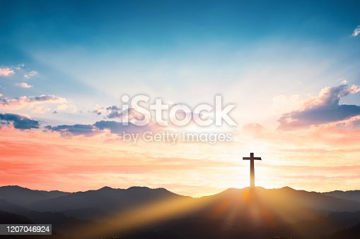 Silhouette cross on mountain sunset background