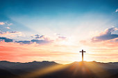 istock Silhouette cross on mountain sunset background 1207046924
