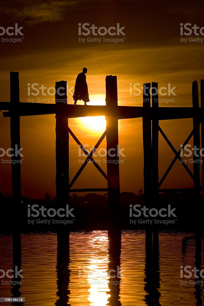Silhouette crossing woden bridge at sunset stock photo