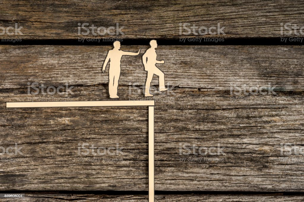 Silhouette cutout men standing next to each other as one pushes another off the edge stock photo