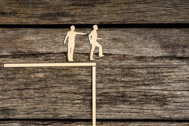 Hombres de corte de silueta de pie al lado de uno como uno empuja a otro fuera del borde - foto de stock