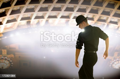male dancer poses on stage with derby hat.