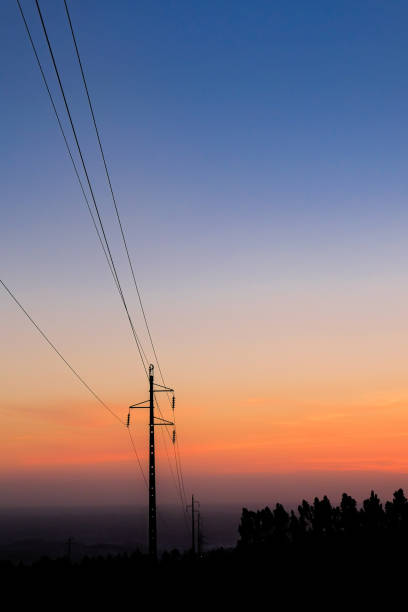 silhouette electricity pole, electricity pylons technology on sunset time background stock photo