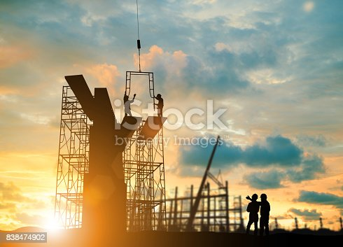 istock Silhouette engineer  look team construction safely to work load scaffolding over blurred background sunset pastel for industry background with Light fair 838474902