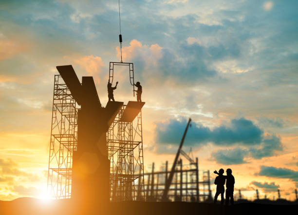 Silhouette engineer  look team construction safely to work load scaffolding over blurred background sunset pastel for industry background with Light fair stock photo