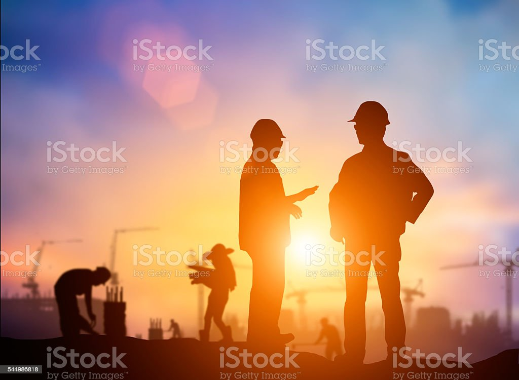 silhouette engineer looking Loaders and trucks in a building sit silhouette engineer looking Loaders and trucks in a building site over Blurred construction worker on construction site Adult Stock Photo