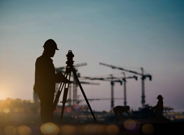 silhouette engineer looking loaders and trucks in a building site over blurred construction worker on construction site - perito foto e immagini stock