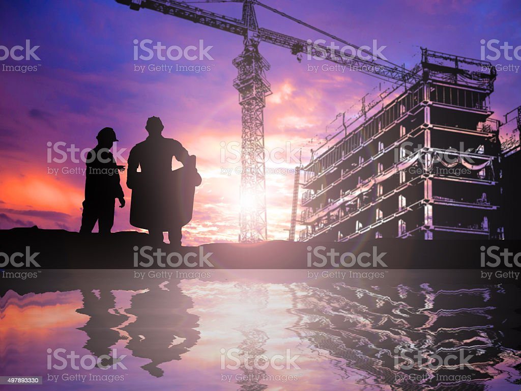 silhouette engineer working  in a building site over Blurred con stock photo