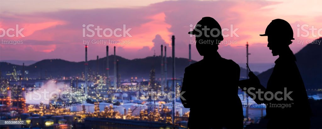Silhouette engineers are standing orders The oil refining industry stock photo