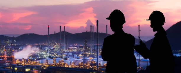 silhouette engineers are standing orders the oil refining industry - refinery stock photos and pictures